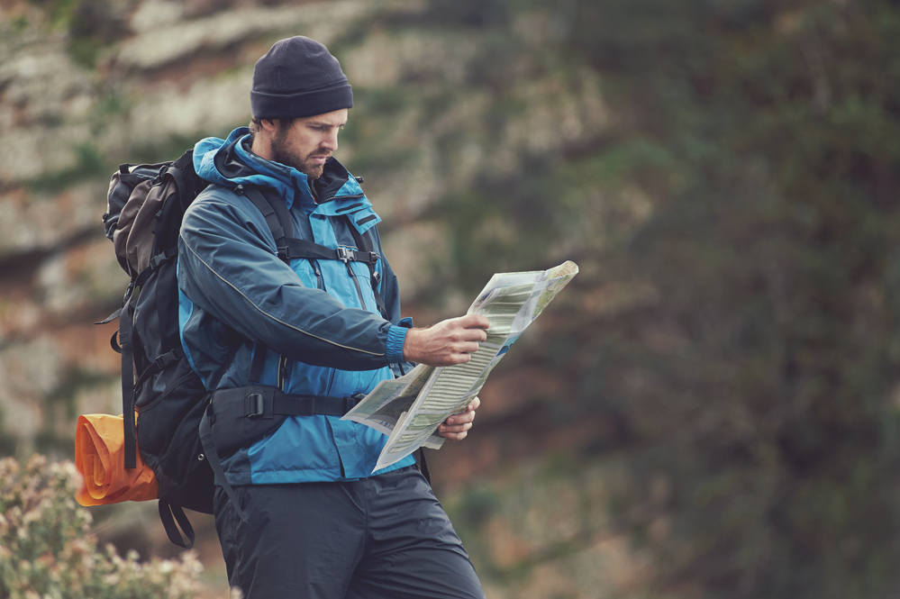 Man reads a map while backpacking